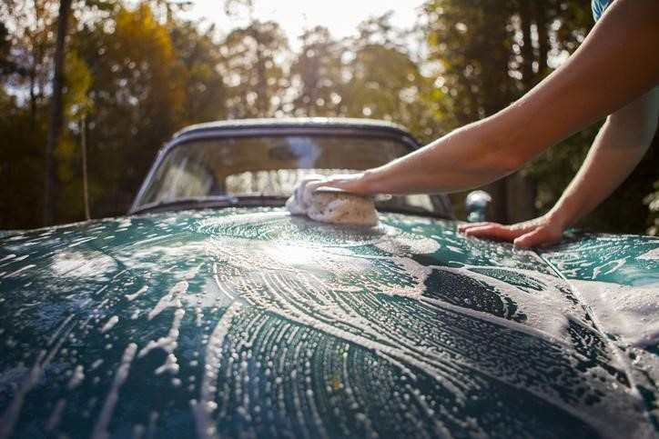 Washing a car by hand with sponge and soapy water with forest in the background.
