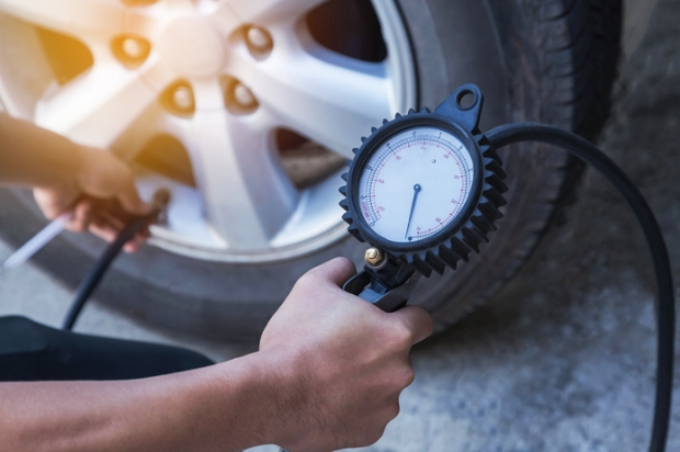 Checking tyre air pressure with pressure gauge