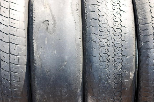 A row of worn out tyres with uneven tread patterns