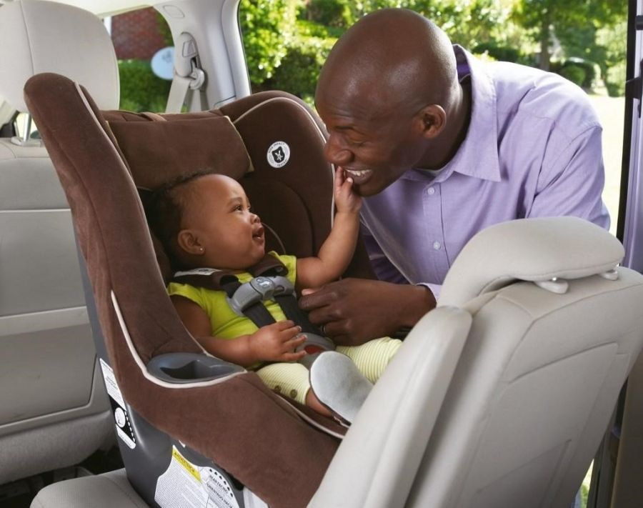 Father placing child into child car seat in rear of car
